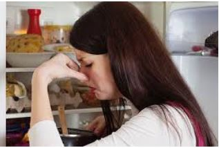 woman pinching her nose at spoiled food